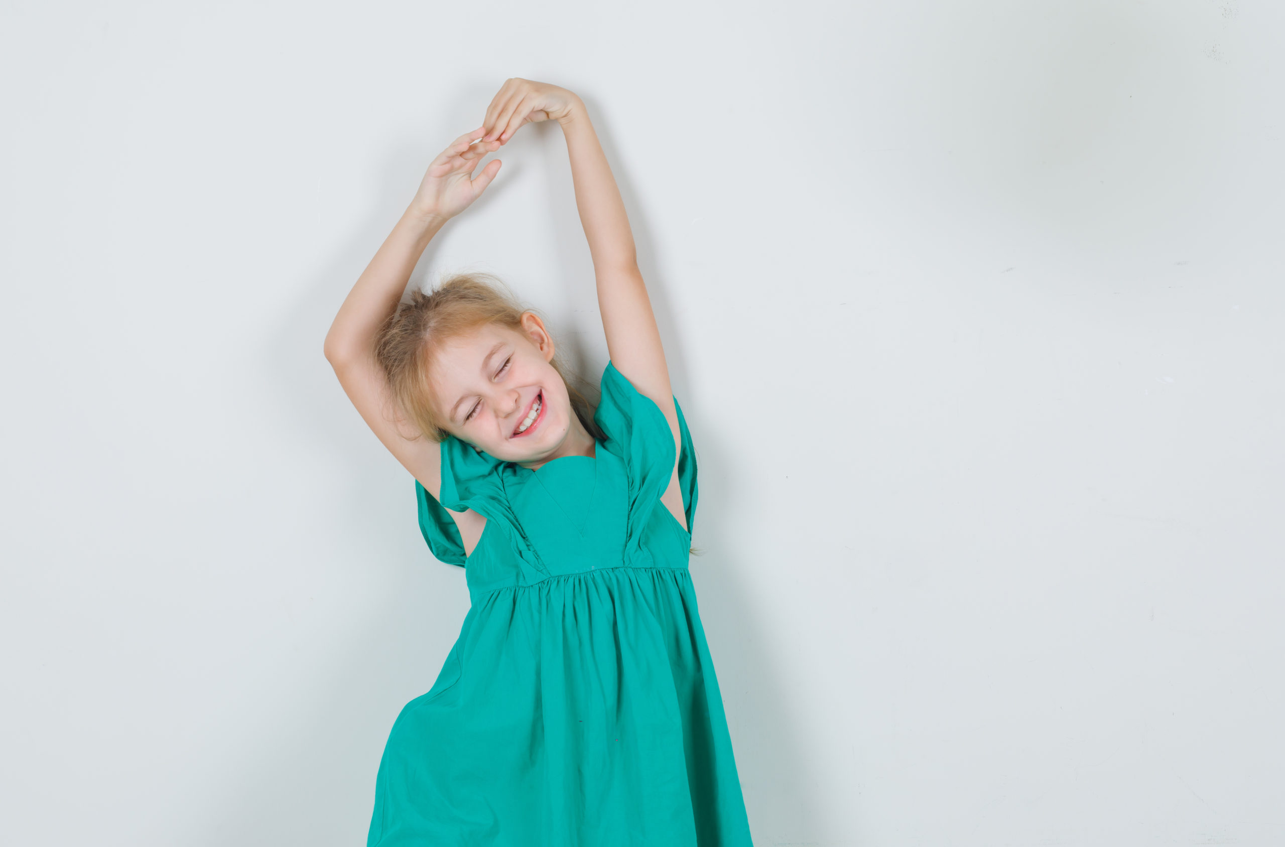 Little girl in green dress stretching arms with closed eyes and
