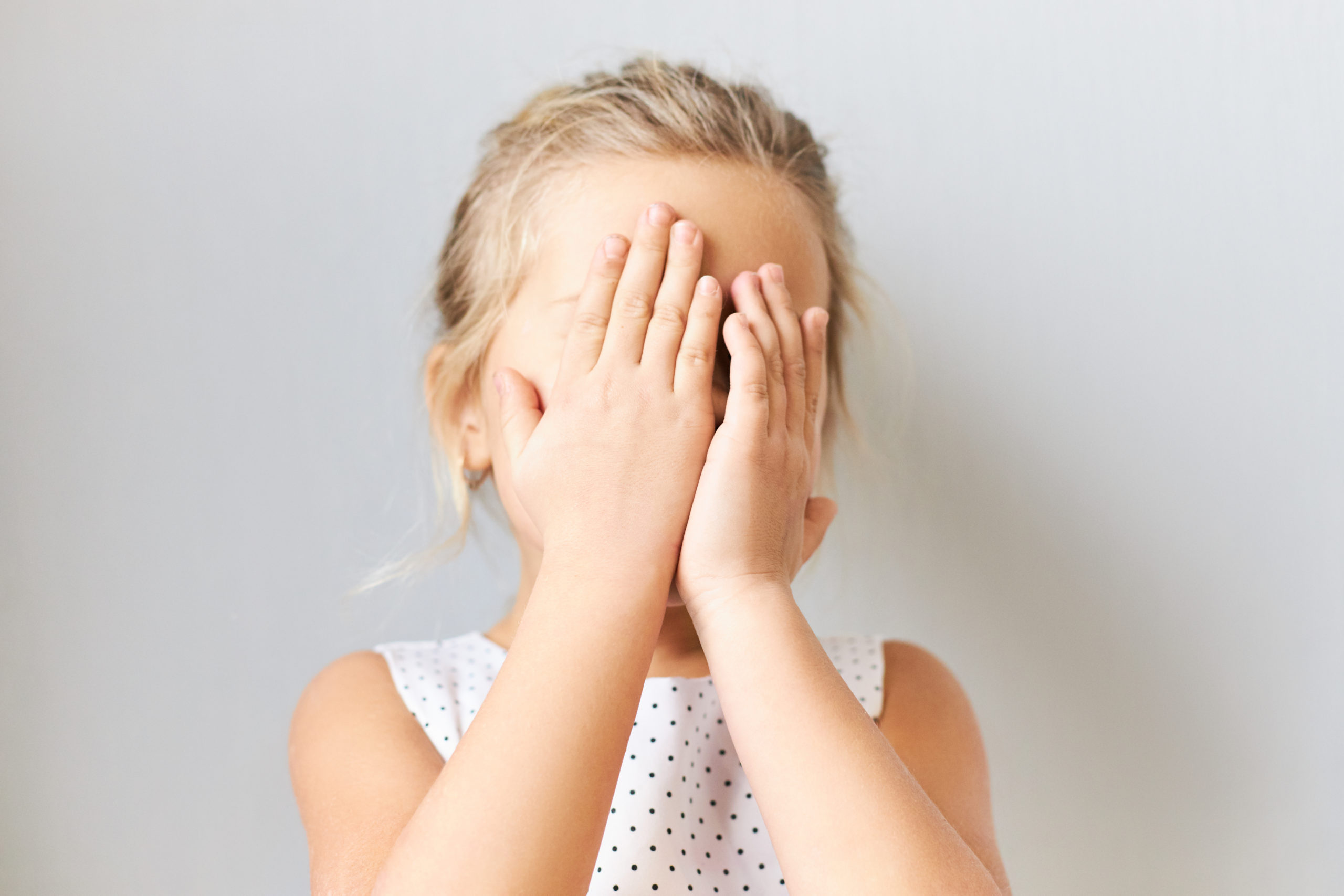Shy timid little girl covering face, feeling scared. Embarrassed female kid posing isolated with hands on her eyes, crying, feeling ashamed because mother telling her off. Baby playing hide and seek